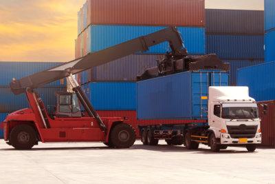 スタッカーは、コンテナ内の運搬シャーシに配置するために、40インチの高さの青いキューブコンテナーを使用しています。