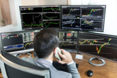 取引統計を見ながら電話を持つ実業家