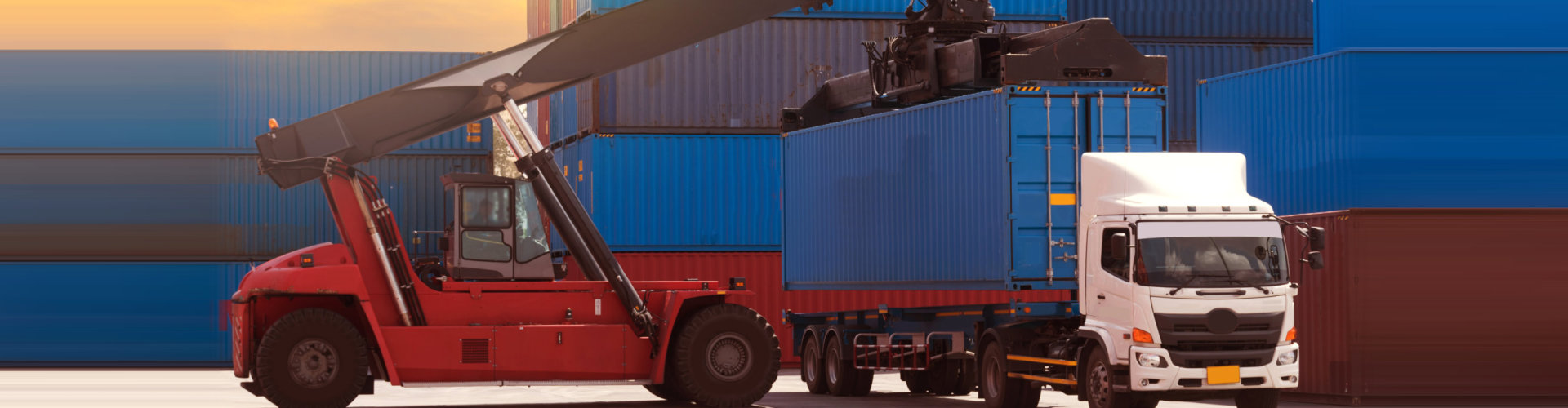 stacker is taking blue 40' high cube container to put on haulage chassis inside container