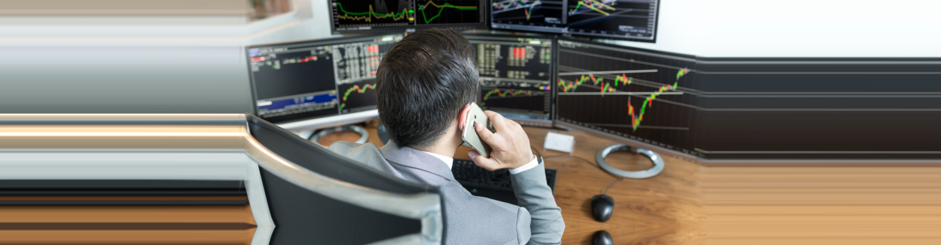 businessman having a phone call while looking the trading statistic